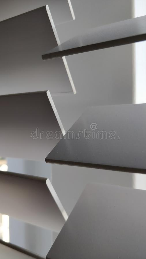 Shutter panels switched half open. Close up of two white shutter panels switched half open royalty free stock image