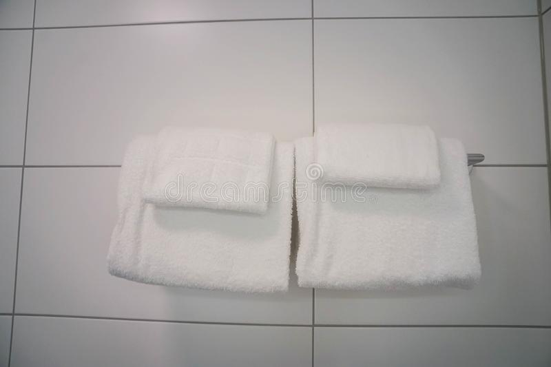 Two white soft cotton towel on bathroom rail for shower stock images