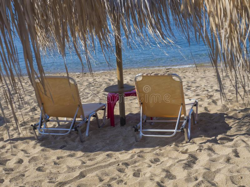 Close up two yellow empty sunbeds with sun umbrella on greek sandy beach with turquoise clear blue sea water.  royalty free stock image