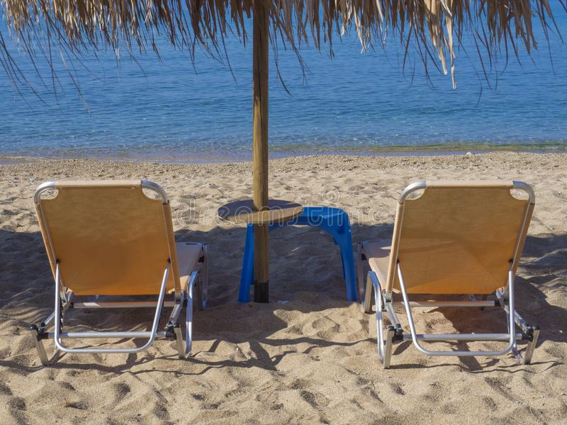 Close up two yellow empty sunbeds with sun umbrella on greek sandy beach with turquoise clear blue sea water.  stock images
