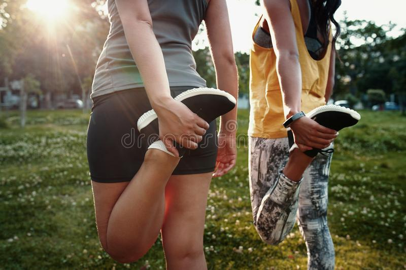 Close-up of two young females stretching their legs - two sporty woman stretching their quads before running. Two young women stretching her legs in the park royalty free stock photography