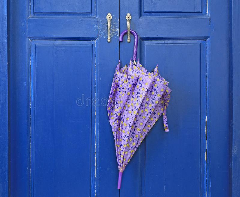 Close up Umbrella hanging on wood door. Ready to be picked up during rain stock photos