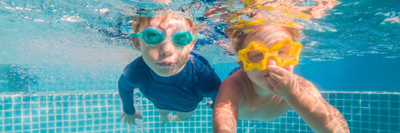 Close-up underwater portrait of the two cute smiling kids BANNER, LONG FORMAT. Close-up underwater portrait of the two cute smiling kids. BANNER, LONG FORMAT stock image