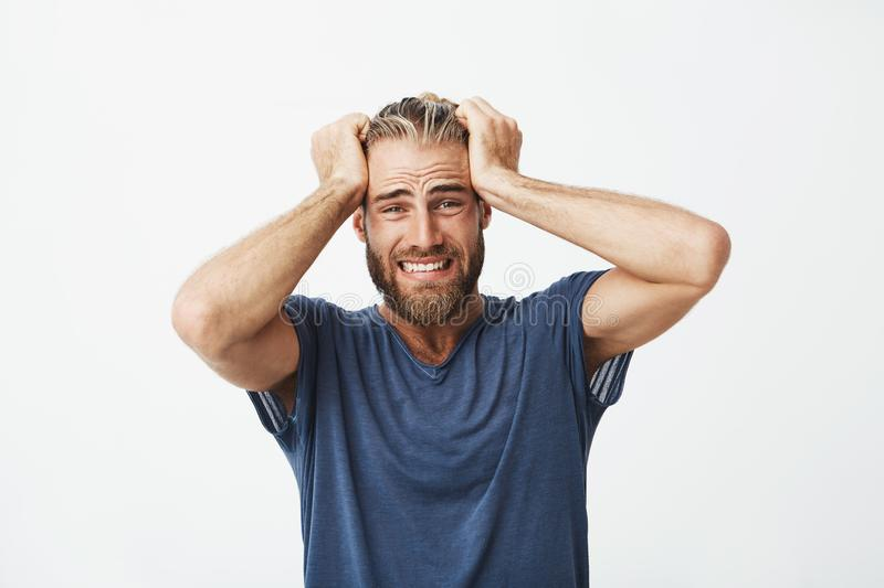 Close up of unhappy handsome guy with beard holding hair with hands, being super disappointed about broken new royalty free stock photography