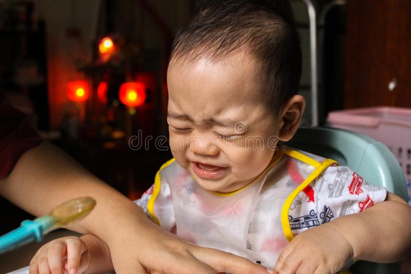 Close up of unhappy little seven months old son in see through plastic bib screaming and crying in chair for babies after mom made stock photo