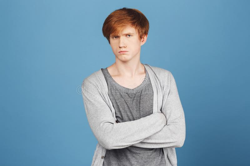 Close up of unhappy young good-looking ginger boy in casual stylish outfit crossing hands, looking in camera with stock images