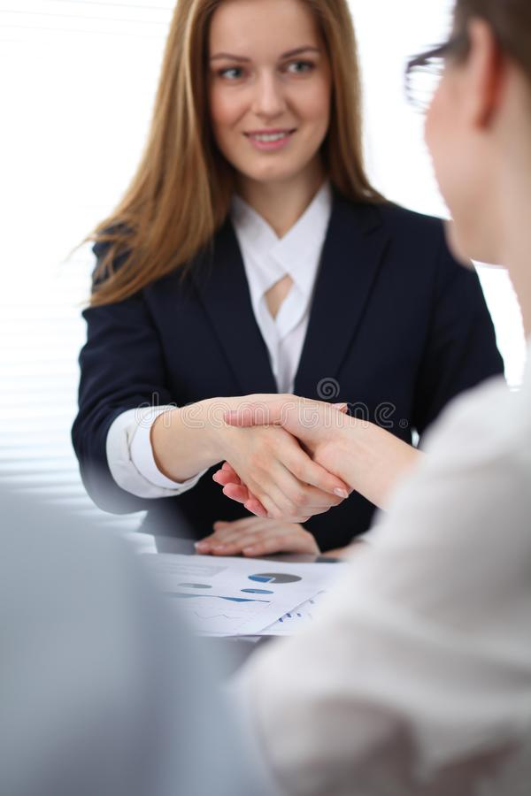 Close Up of unknown business people shaking hands while finishing up a meeting. Handshaking, agreement or success royalty free stock image