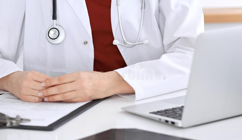 Close-up of a unknown female doctor`s hands. Physician at working place ready to consult and halp patients. Medicine. Concept royalty free stock photography