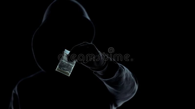 Close-up of unknown man showing packet with heroine at camera, drug dealer royalty free stock image