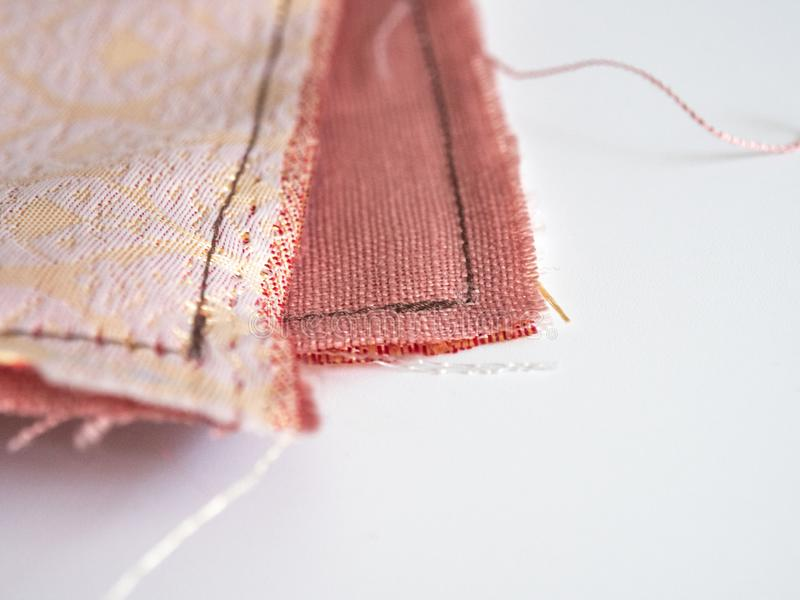 Close up of unravel pink-orange linen fabric texture with brown thread stitches with copy space. Materials, textiles and garment. Concept royalty free stock photography