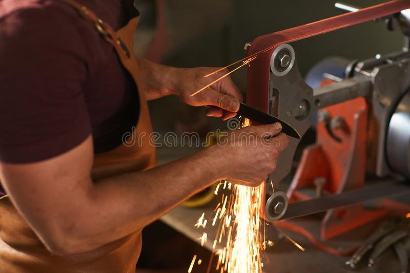 Using knife grinding jig. Close-up of unrecognizable artisan in apron using knife grinding jig to sharpen knife blade in smithy stock photo