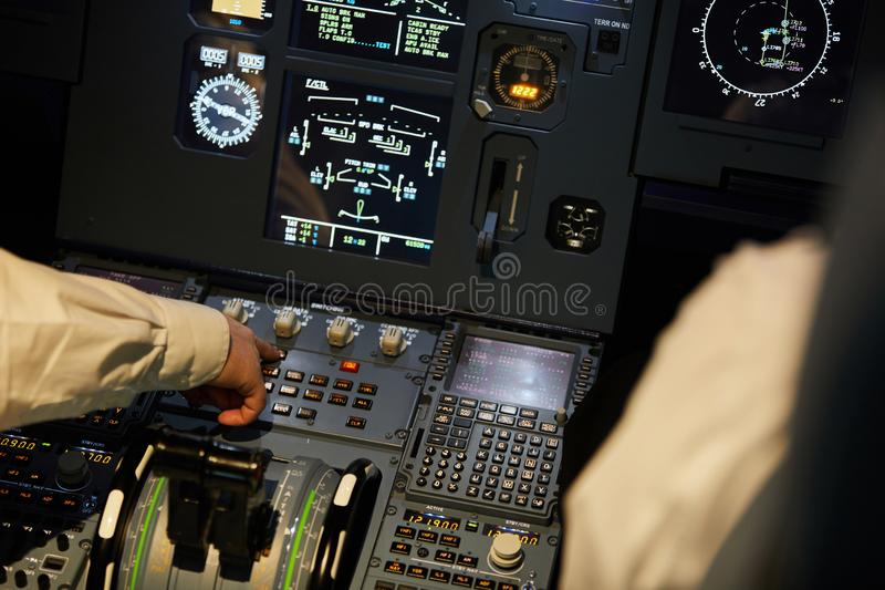 Aviators checking engine systems on flight deck. Close-up of unrecognizable aviators sitting at control panel with digital displays and checking engine systems royalty free stock photos