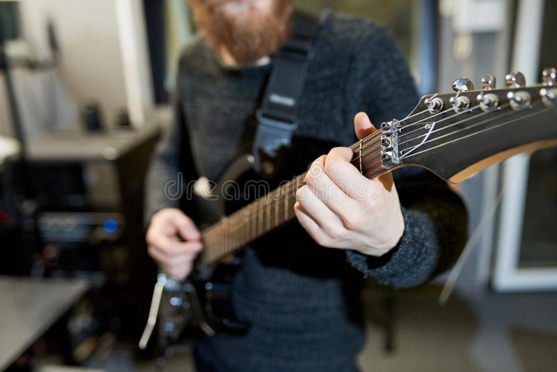 Skilled man playing electric guitar in studio. Close-up of unrecognizable hipster musician composing new melody while playing electric guitar and holding fingers stock photography