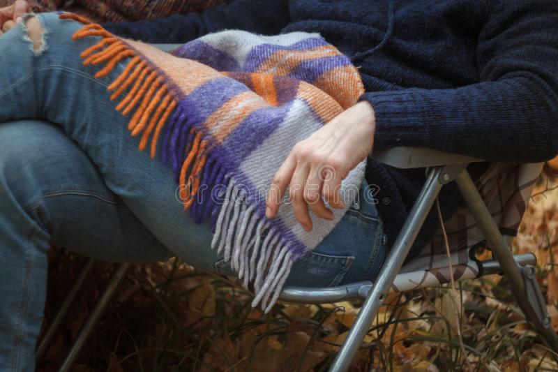 Close-up of an unrecognizable man in jeans and a sweater sitting on a folding deck chair in the autumn in the forest, a cozy royalty free stock photos