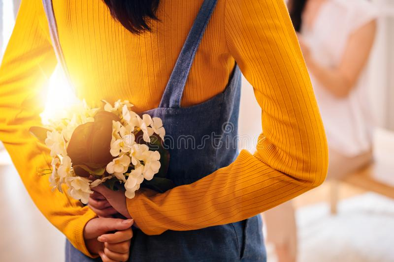 Teenage girl hiding beautiful flowers behind for pleasant surprise to her mother stock image
