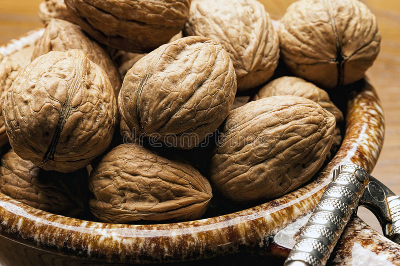 Close up of unshelled walnuts. A close up of walnuts in their shells in a bowl stock photography