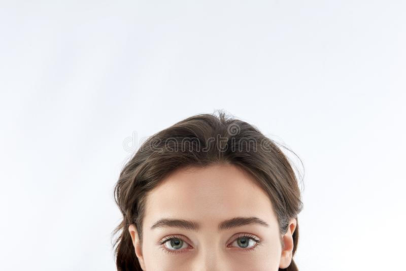 Upper face of young pretty brunette female stock images