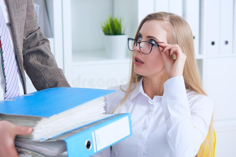 Close up of upset business woman taking folders with papers from male colleague`s hand in office. Business, people and stock photography