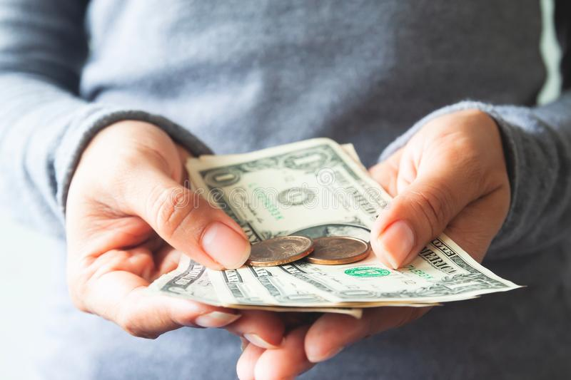 Close up US dollar bills and coins on woman hands. Business and stock photo