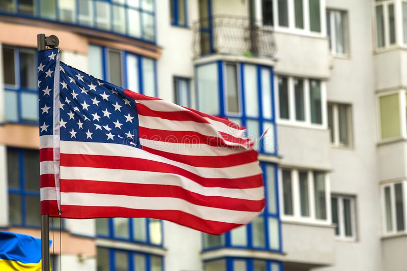 Close up of the us flag against city skyline.  stock photos