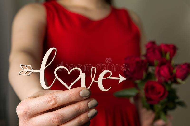 Valentines day love sign and red roses, beautiful woman in red dress holding love cupid arrow in hand,close up. Close up Valentines day love sign, beautiful stock photo