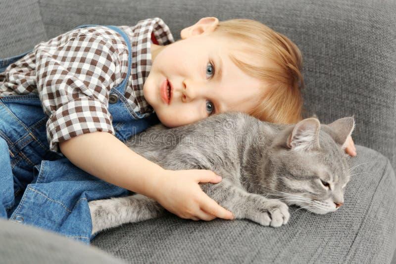 Close-up van aanbiddelijk weinig jongen met leuke kat op grijze leunstoel stock foto's