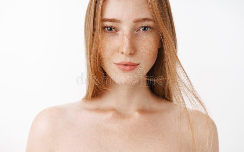 Close-up van aantrekkelijke vrouwelijke naakte roodharigevrouw wordt geschoten met sproeten die over grijze achtergrond die sensu royalty-vrije stock afbeelding