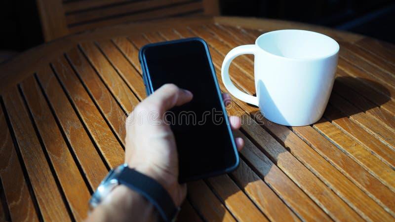 Close-up van Aziatische mannelijke handen die smartphone spelen en koffie drinken bij een openluchtlijst met ochtendzonlicht stock foto's