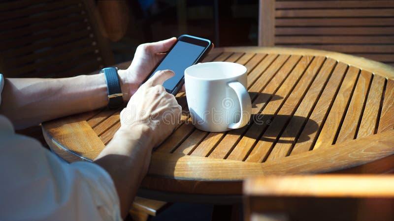 Close-up van Aziatische mannelijke handen die smartphone spelen en koffie drinken bij een openluchtlijst met ochtendzonlicht royalty-vrije stock foto's