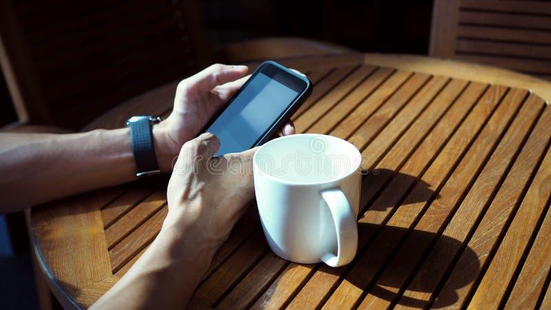 Close-up van Aziatische mannelijke handen die smartphone spelen en koffie drinken bij een openluchtlijst met ochtendzonlicht stock foto