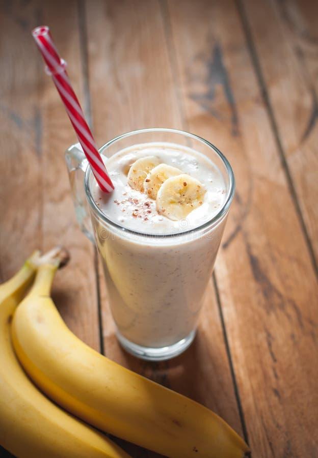 Close-up van banaan en lijnzaad smoothie in een glas op houten achtergrond stock afbeelding