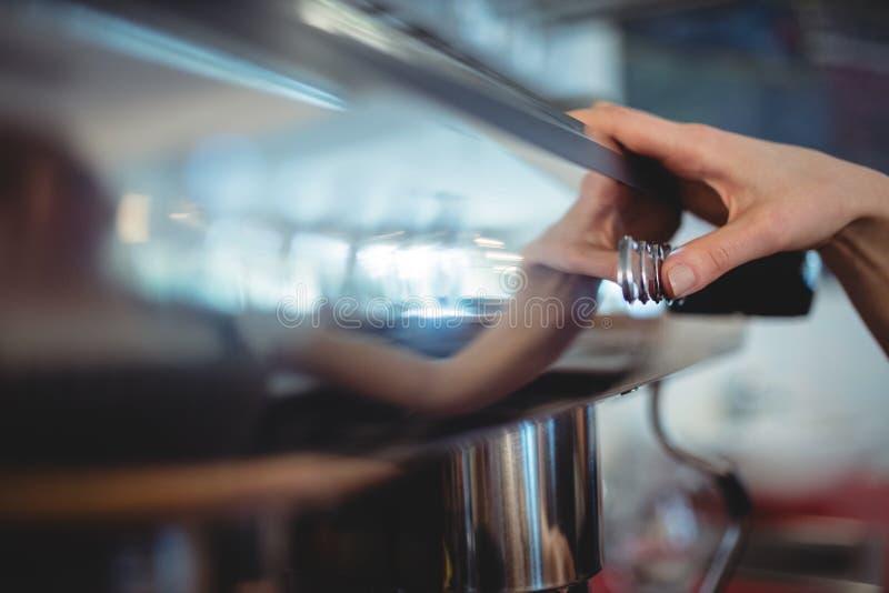 Close-up van barista duwende knoop op koffiezetapparaat bij cafetaria royalty-vrije stock foto