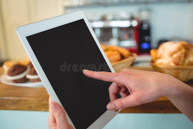 Close-up van baristavinger het scrollen tabletpc bij koffie stock fotografie