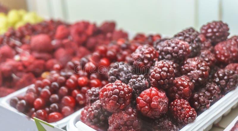 Close-up van bevroren fruit in supermarkt Blackberry in nadruk, vage Raspberrie royalty-vrije stock afbeelding