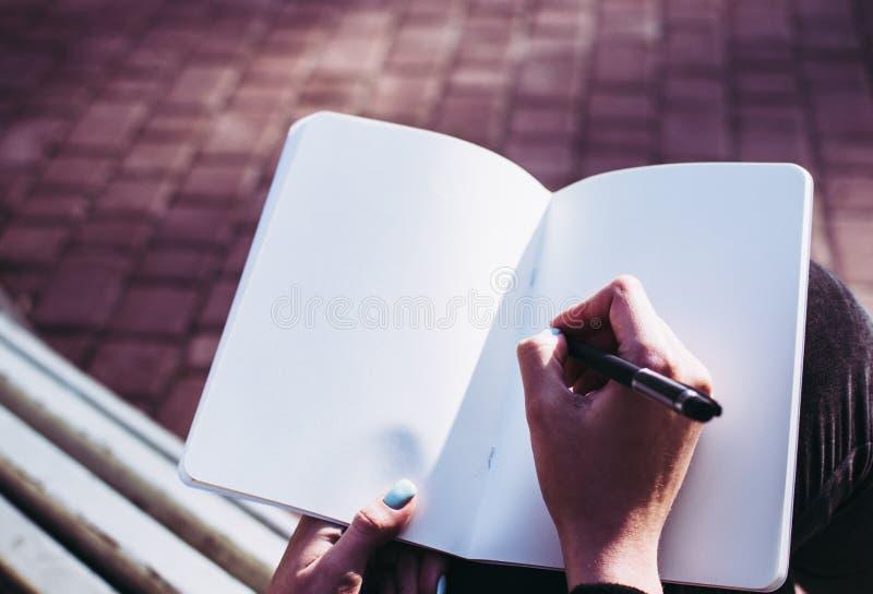 Close-up van blanco pagina's van een notitieboekje en van het meisje hand die haar gedachten en ideeën beginnen neer te schrijven stock foto