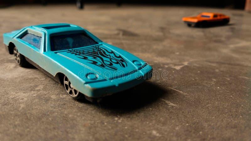 Close-up van blauwe stuk speelgoed auto voor kinderen op diverse achtergrond met oranje stuk speelgoed auto op achtergrond stock fotografie