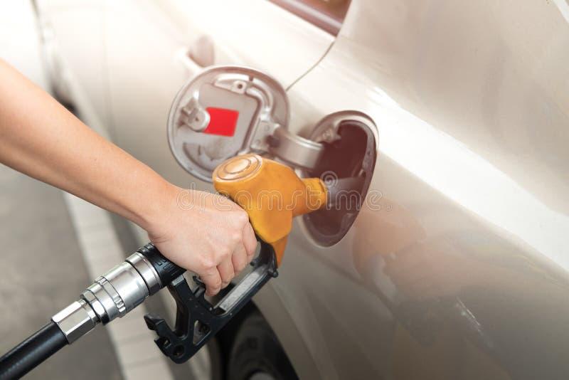 Close-up van brandstof van de mensen de pompende benzine in auto bij benzinestation brandstof stock foto's