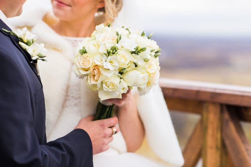 Close-up van bruidhanden die het mooie boeket van het de winterhuwelijk houden royalty-vrije stock foto