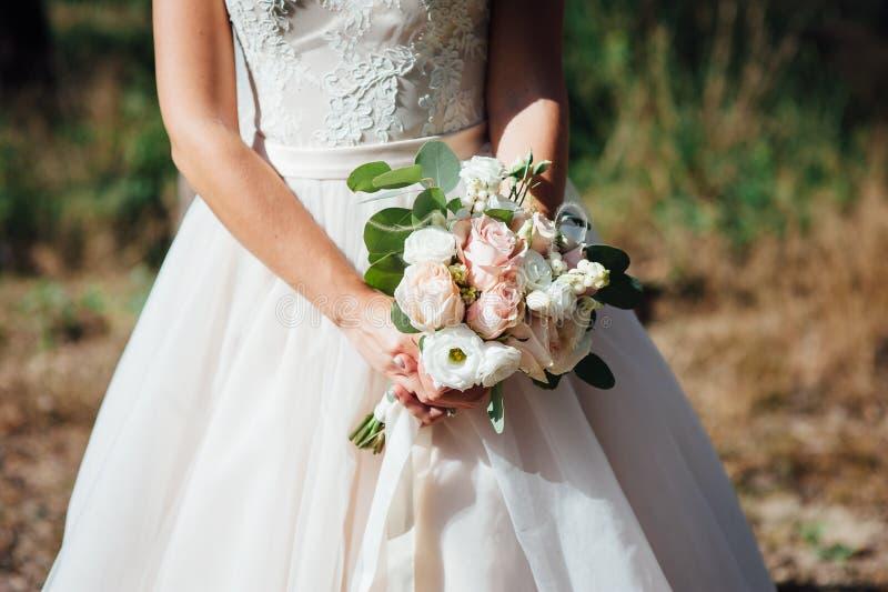 Close-up van bruidhanden die mooi huwelijksboeket houden royalty-vrije stock afbeelding
