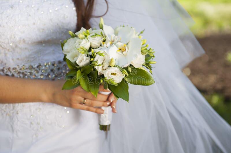 Close-up van bruidhanden die mooi huwelijksboeket houden stock foto's