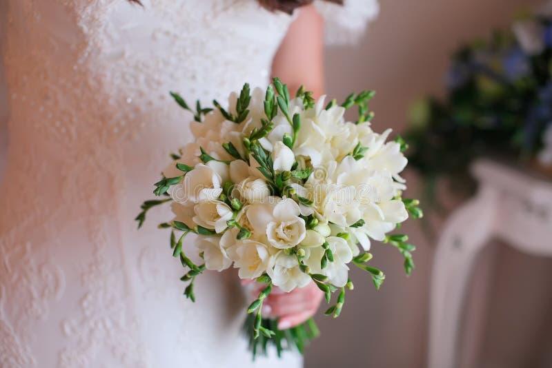 Close-up van bruidhanden die mooi huwelijksboeket houden stock afbeelding