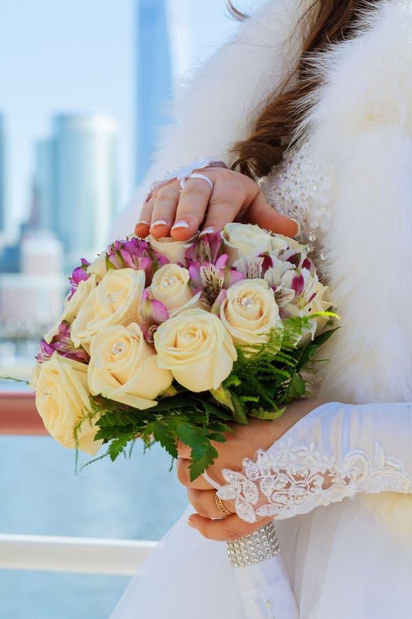 Close-up van bruidhanden die mooi huwelijksboeket houden stock fotografie