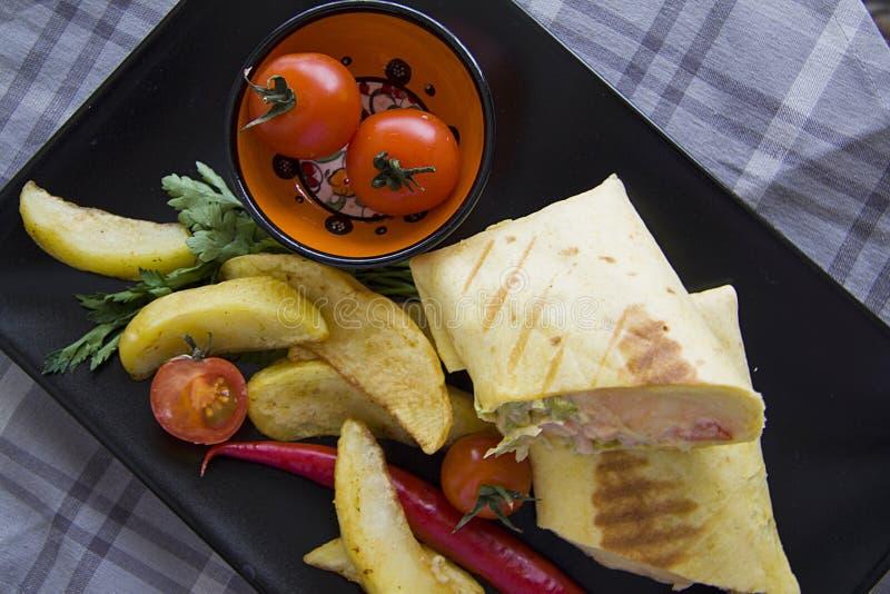 Close-up van burrito met gebraden aardappel op zwarte plaat stock foto's