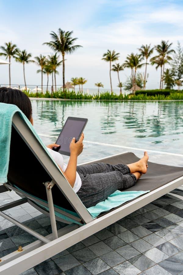 Close-up van de Aziatische tablet van de vrouwenholding bij mooi zwembad stock foto