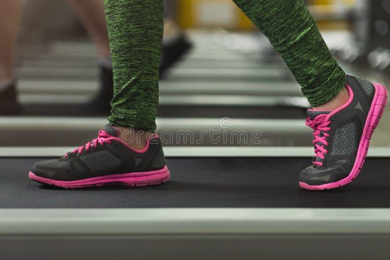 Close-up van de benen die van de geschiktheidsvrouw op tredmolen bij gymnastiek lopen royalty-vrije stock foto's