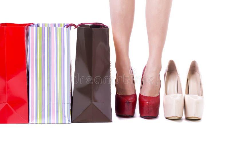 Close-up van de benen van de vrouwenklant, hoge hielen en het winkelen zakken royalty-vrije stock foto's