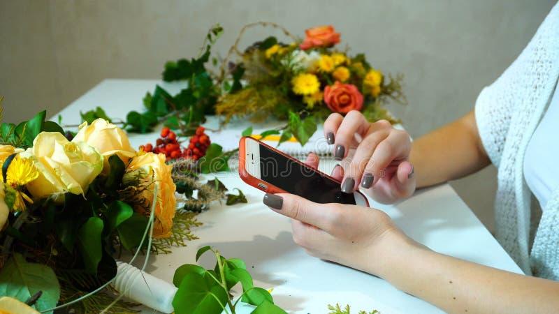 Close-up van de bloemenhanden wordt geschoten die van het ontwerpermeisje ` s dat cellphon gebruikt royalty-vrije stock foto