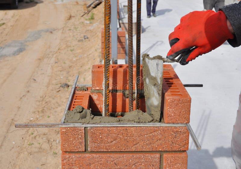Close-up van de Blokken van Metselaarsworker installing red bricklaying stock foto's