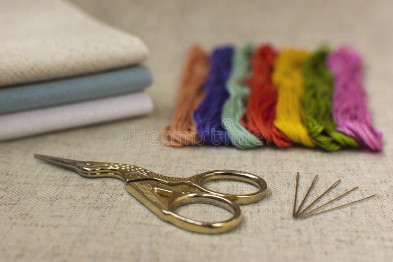 Close-up van de borduurwerk en dwars-steekuitrusting op een natuurlijke lin stock foto's