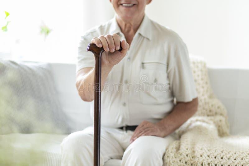 Close-up van de glimlachende en gelukkige hogere mens met wandelstokduri stock foto